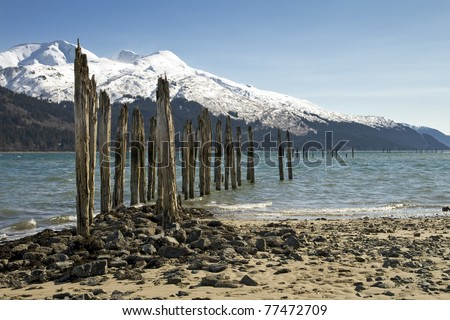 An old pier at a mine in Juneau, Alaska against a mountain backdrop.