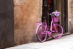 an old pink bike standing on the street