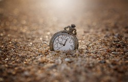 An old pocket watch dropped on the sand, in warm light and bokeh background - thinking and controlling the concept of time.