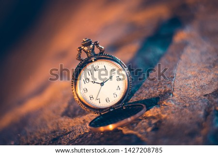 An old pocket watch photographed close to the blurred background