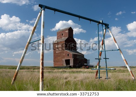 An old prairie grain elevator framed by a swing set.  This is from the ghost town of Bents in Saskatchewan, Canada. - stock photo