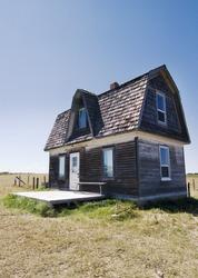 An old prairie house on a grass meadow in Saskatchewan