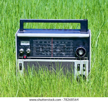 An old radio in the green grass closeup