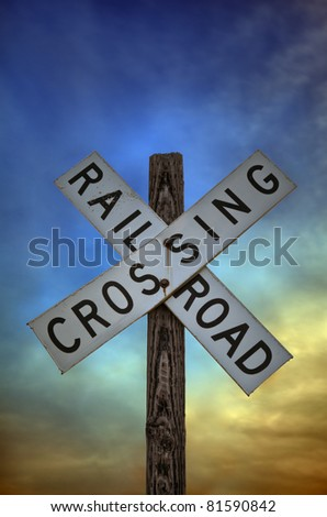 An old railroad crossing sign in front of a dramatic sunset sky.