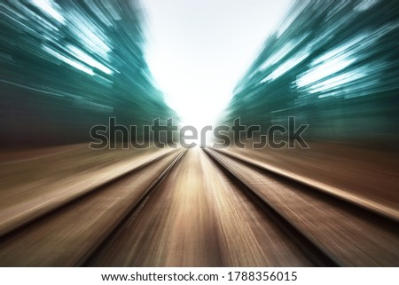 An old railroad through the evergreen forest in a thick morning fog. Abstract art, motion blur, defocus effect. Emptiness, loneliness, horror concepts stock photo