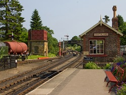 An old railway station with signal box, water tank and goods wagon