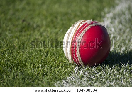 An old red and white cricket ball with worn stitching sits abandoned on the sports field boundary
