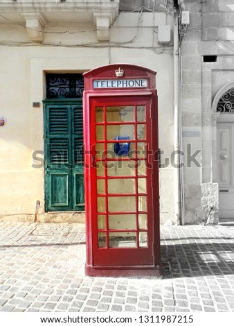 An old, red phone cabin in the island of Malta. Half of the picture is in color and the other half in black and white