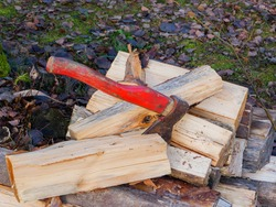 An old red shabby axe on a pile of firewood.