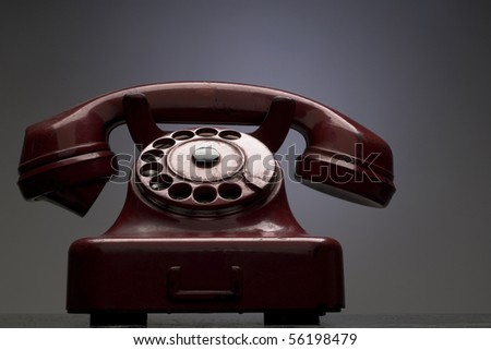 an old red telephone against gray background
