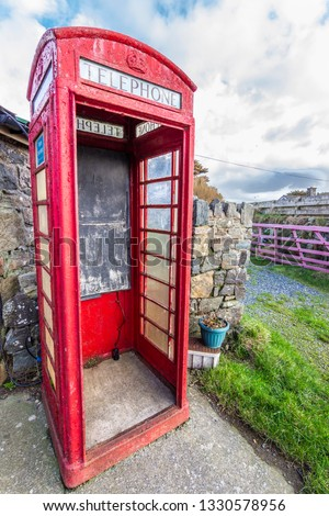 An old red telephone cabin typical in the United Kingdom but right now part of the history as a nice stamp of the past telephone days. A nice cloudy outdoor background typically English