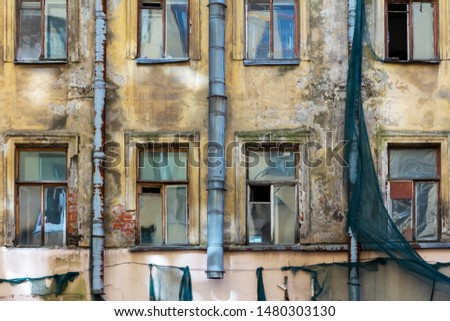An old residential building awaiting reconstruction or demolition. Facade with windows of crumbling plaster, scraps of green protective mesh and rusty drainpipes