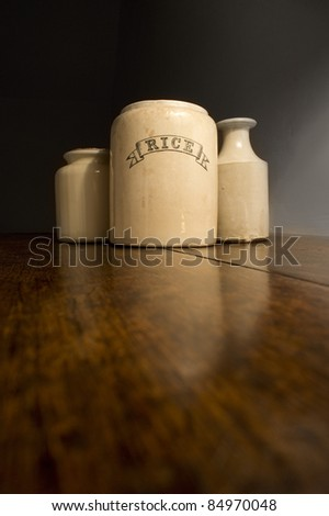 an old rice pot and other pots on a dark wooden shelf