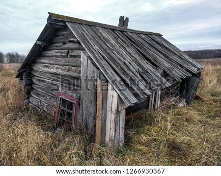An old rickety dilapidated residential log wooden house. Russia