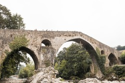An old Roman stone bridge in Cangas de Onis over the river in Spain