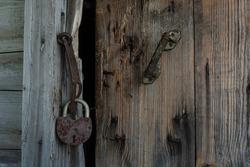 an old rotten wooden door with a broken lock
