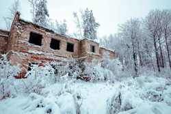 An old ruined building in a snowy forest.