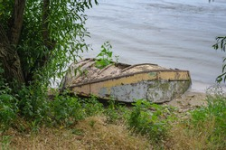An old ruined wooden boat on the shore. A small fishing boat lies upside down.