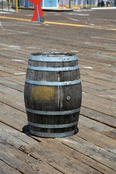 An old Rum Barrel sits on a wooden board walk. old dirty wooden keg or rum barrel.