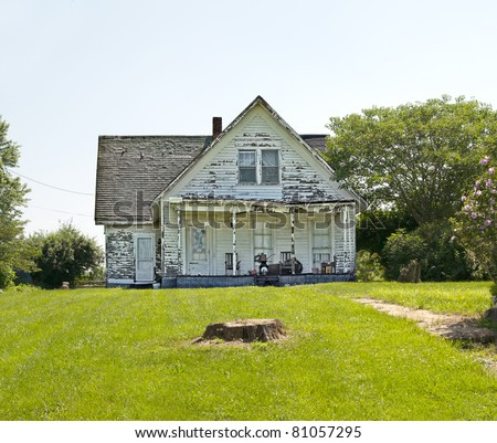 Photo of  An old run down, weather beaten wood siding house that is in need of repair.  What a realtor would refer to as a fixer-upper.