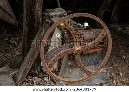 An old rusted iron wheel placed against other vintage objects at an historical heritage listed homestead