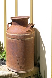 An old rusted milk can is next to an exterior wall.