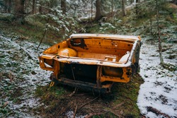 An old rusted out scrap car that has been abandoned in the woods. Car wreck abandoned in the woods.