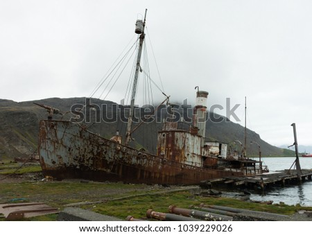 An old, rusted whaling boat no longer in use on the shore at Grytviken, South Georgia. Fog, a hillside and the bay are in the background. #1039229026
