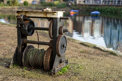 An old rusty Barge winch next to a canal used as part of an old canal lock