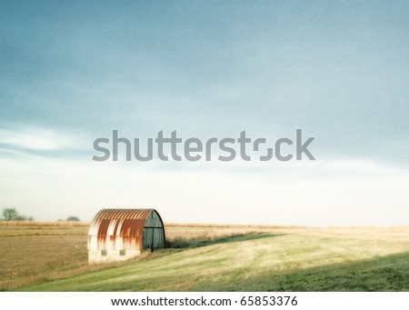 An old rusty barn or shed sitting in the middle of a barren field in what is a pastoral autumn setting.