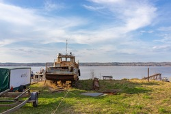 An old rusty boat at the boat station. The bank of the Chusovaya River. Landscape with a blue sky and green grass.