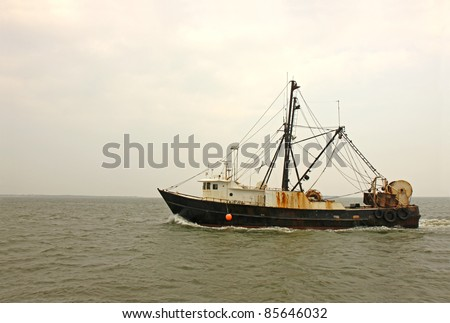 An old, rusty fishing trawler heads for home on Pamlico Sound, North Carolina against the gray mists of an early morning sky
