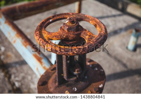 An old rusty gas control valve on the wall. Industrial valve in a large system. Rusty pipes. Old water valve.
