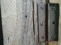 An old rusty hinge on a wooden window. Building material concept
