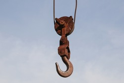 An old rusty hook of a hoisted crane in the port.