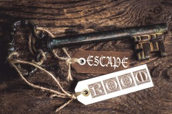 an old rusty key on a ribbed wooden table and  labels with the text Escape room