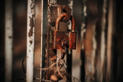 An old rusty metal padlock hangs on an old abandoned gate in the gloomy weather of autumn. Fearfully.