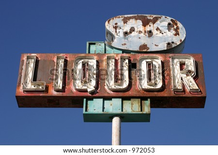 "An Old Rusty Neon ""Liquor"" sign still stands against a beautiful blue sky in California"