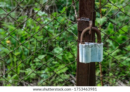 An old rusty padlock hangs on a rusty hinge, a rusty gate against a rusty mesh background and green grass mixed with dry old grass.