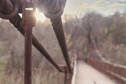 An old rusty steel bridge cable attachment at sunset or sunrise in early spring or late fall