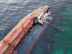 An old rusty tanker lies on the beach sideways. The storm-swept vessel pollutes the water with oil flowing from the tanks.