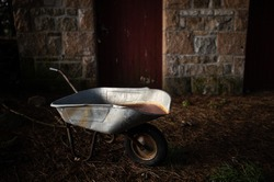 An old rusty wheelbarrow in front of barn in the forest, high contrast