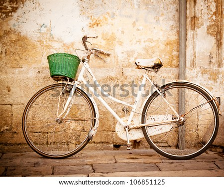 An old, rusty white bicycle with a basket leaning against a grungy wall in Italy.