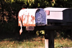 An old, rusty white metal mailbox in the sunlight with a black and green background on a summer day.