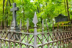 An old rusty wrought-iron cemetery fence on an overgrown grave with a cross and a crypt. Lutheran cemetery in St. Petersburg, Russia