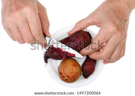 An old senior man cuts with a knife boiled vegetables- potato and beet . Isolated on white studio concept