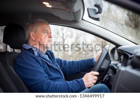 An old senior man driving a modern car, transportation concept