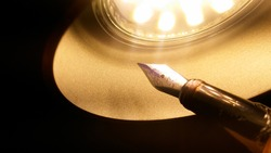 An old shiny fountain pen featuring a golden metal nib illuminated by the warm yellow light of a LED lamp in the conical form of a cupola ; symbolic image for inspiration in literacy or revelation