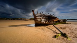 An old shipwreck boat abandoned stand on beach or Shipwrecked off the coast Bad Eddie Shipwreck - An old shipwreck found on the beach at Bunbeg, Donegal in Ireland.