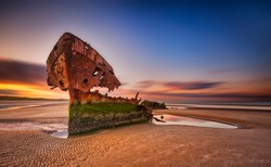 An old shipwreck boat abandoned stand on beach or Shipwrecked off the coast of Ireland